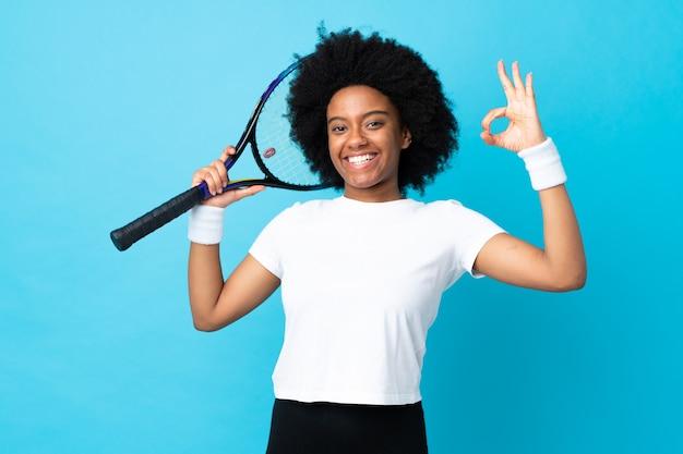 Joven mujer afroamericana aislada sobre fondo azul jugando tenis y haciendo aceptar firmar