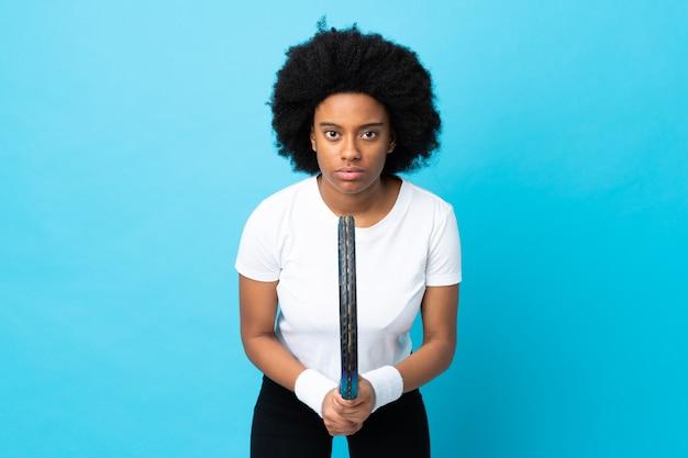 Joven mujer afroamericana aislada sobre fondo azul jugando tenis