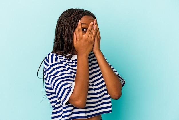 Joven mujer afroamericana aislada sobre fondo azul parpadea a través de los dedos asustada y nerviosa.