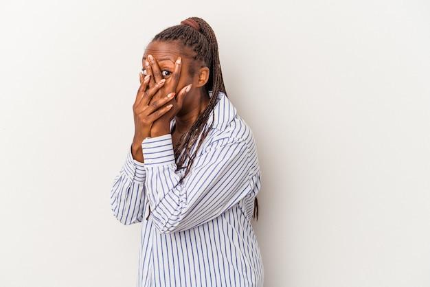 Joven mujer afroamericana aislada sobre fondo blanco parpadea a través de los dedos asustada y nerviosa.