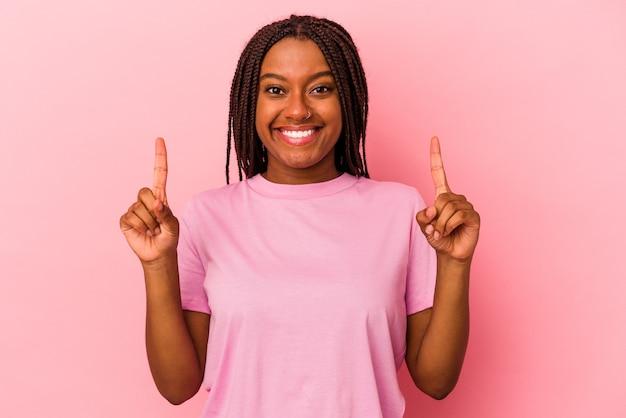 Joven mujer afroamericana aislada sobre fondo rosa indica con ambos dedos hacia arriba mostrando un espacio en blanco.