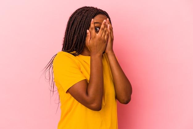 Joven mujer afroamericana aislada sobre fondo rosa parpadea a través de los dedos asustada y nerviosa.
