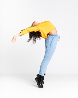 Joven mujer afroamericana bailando sobre pared blanca