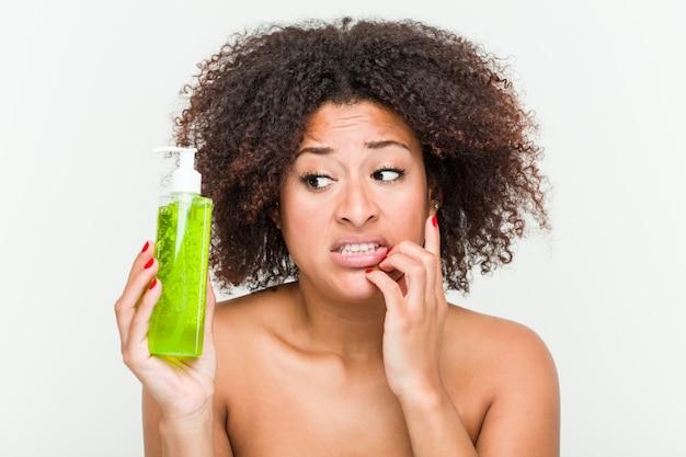Joven mujer afroamericana con botella de aloe vera morderse las uñas, nervioso y muy ansioso.
