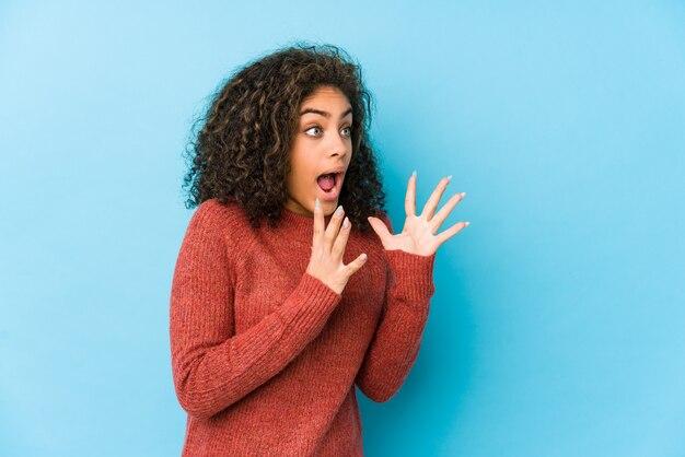 La joven mujer afroamericana de cabello rizado grita fuerte, mantiene los ojos abiertos y las manos tensas.
