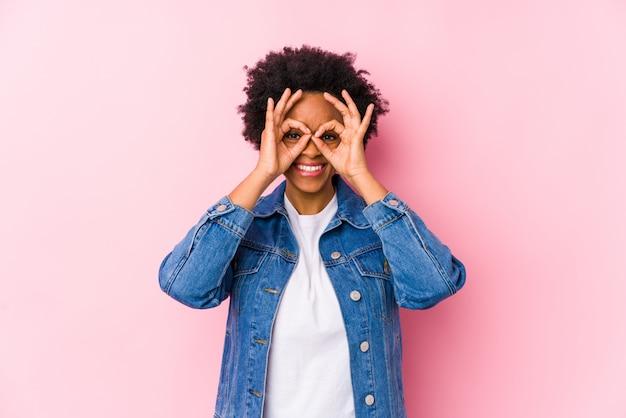 Joven mujer afroamericana contra un fondo de color rosa aislado que muestra signo bien sobre los ojos