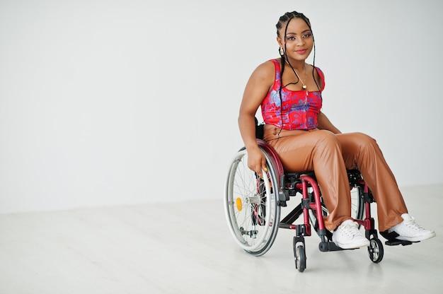 Joven mujer afroamericana discapacitada en silla de ruedas contra la pared blanca.