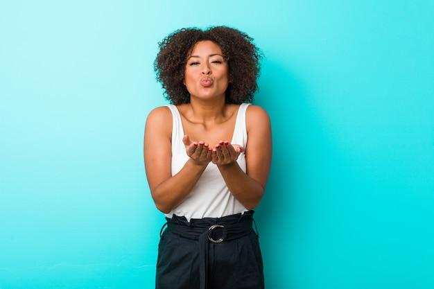 Joven mujer afroamericana doblando los labios y sosteniendo las palmas para enviar beso de aire.