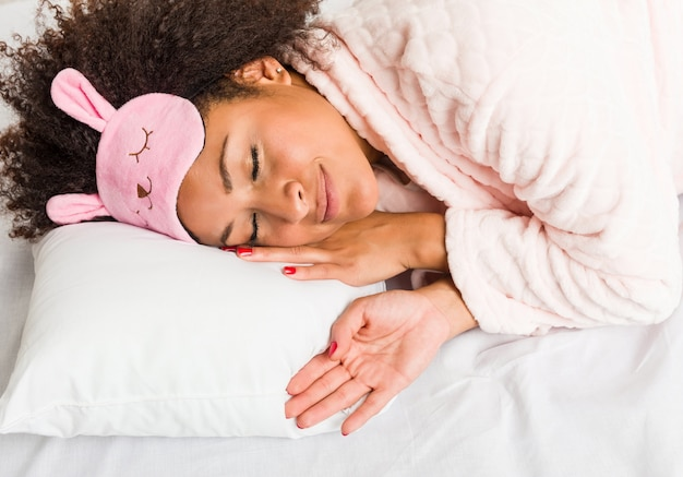 Joven mujer afroamericana durmiendo con una almohada en la cama