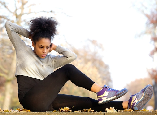 Joven mujer afroamericana ejercicio sit ups