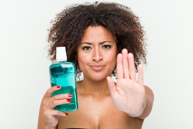 Joven mujer afroamericana con enjuague bucal de pie con la mano extendida que muestra la señal de stop, impidiéndole.