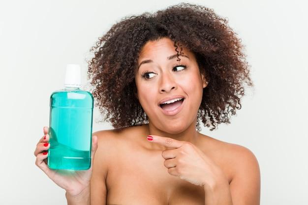Joven mujer afroamericana con enjuague bucal sonriendo alegremente señalando con el dedo lejos.