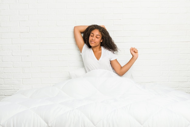 Joven mujer afroamericana se estira en la cama