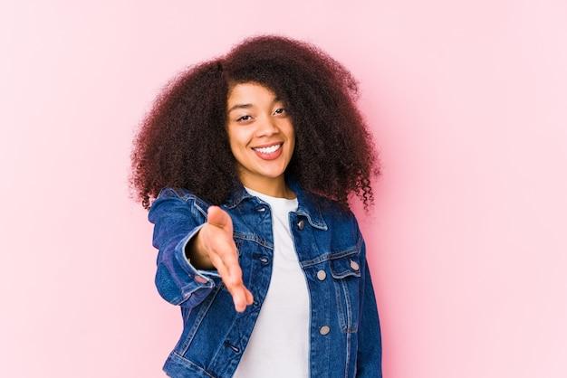 Joven mujer afroamericana estirando la mano a la cámara en gesto de saludo.