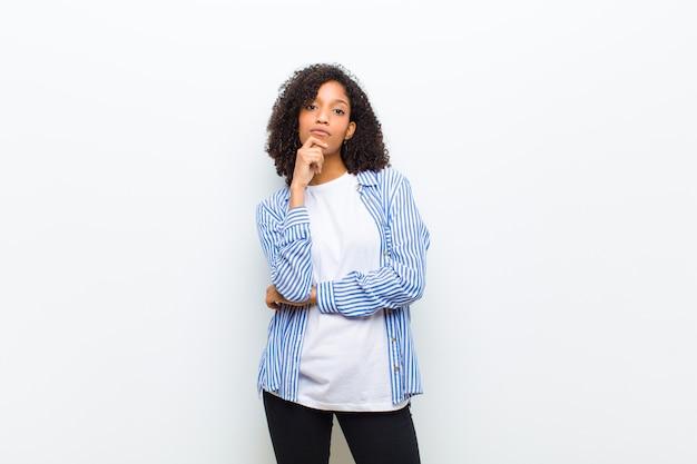 Joven mujer afroamericana fresca pensando, sintiéndose dudosa y confundida, con diferentes opciones, preguntándose qué decisión tomar