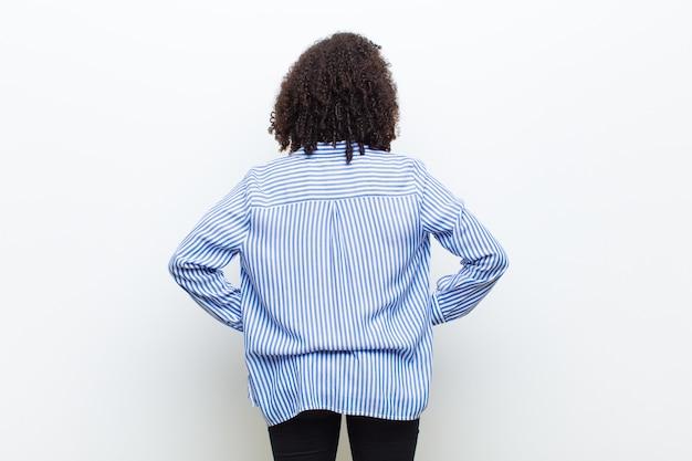 Joven mujer afroamericana fresca sintiéndose confundido o lleno o dudas y preguntas, preguntándose, con las manos en las caderas, vista trasera