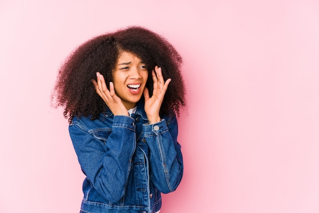 Joven mujer afroamericana grita fuerte, mantiene los ojos abiertos y las manos tensas.