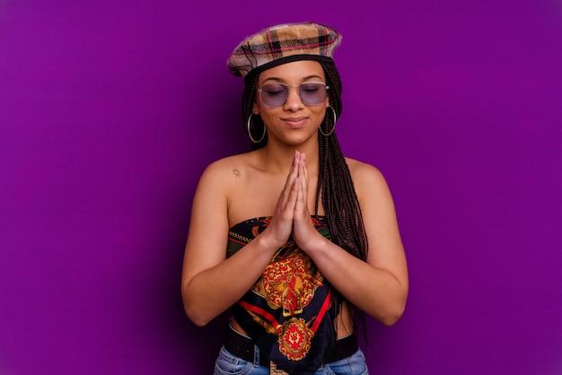 Joven mujer afroamericana joven mujer afroamericana cogidos de la mano en orar cerca de la boca, se siente confiado.