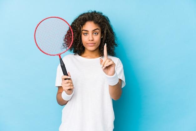 Joven mujer afroamericana jugando bádminton mostrando número uno con el dedo.
