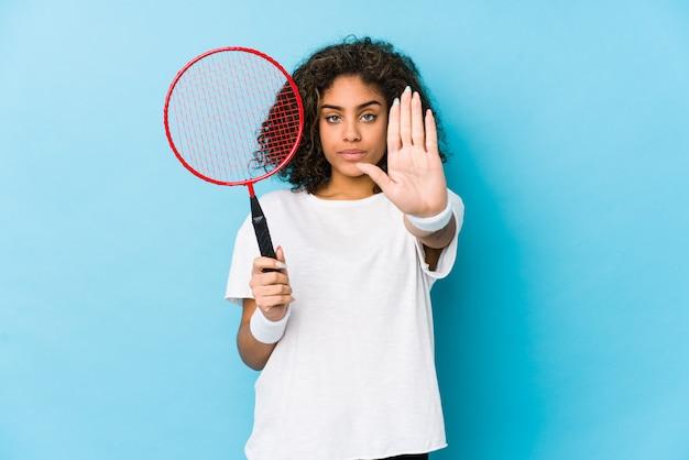 Joven mujer afroamericana jugando bádminton de pie con la mano extendida que muestra la señal de stop, impidiéndole.