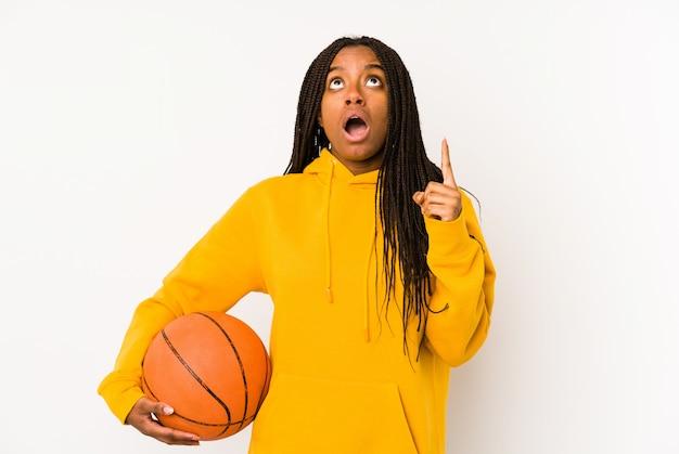 Joven mujer afroamericana jugando baloncesto apuntando al revés con la boca abierta.