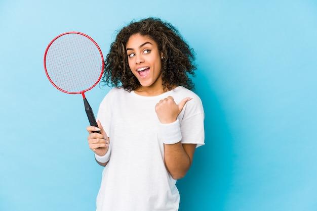 Joven mujer afroamericana jugando puntos de bádminton con el dedo pulgar, riendo y sin preocupaciones.