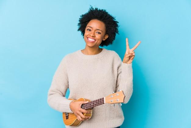 Joven mujer afroamericana jugando ukelele alegre y despreocupado mostrando un símbolo de paz con los dedos.