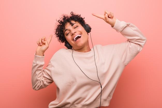 Joven mujer afroamericana con una marca de nacimiento bailando y escuchando música con auriculares