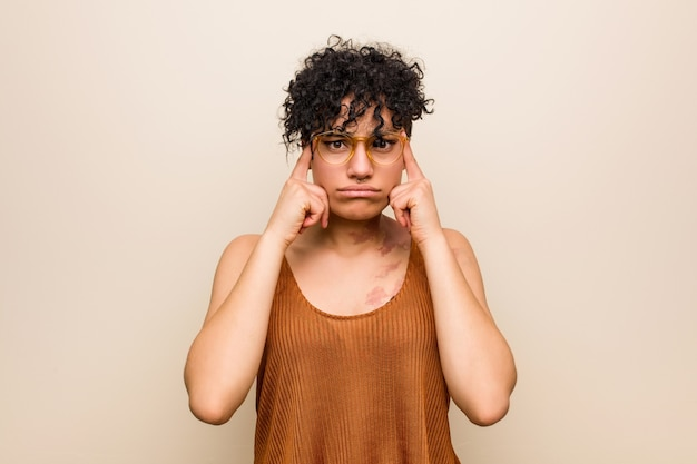 Joven mujer afroamericana con marca de nacimiento de la piel se centró en una tarea, manteniendo los dedos índice apuntando la cabeza.