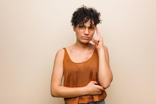 Joven mujer afroamericana con marca de nacimiento de piel señalando el templo con el dedo, pensando, centrado en una tarea.