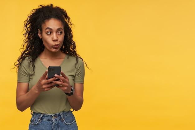 Joven mujer afroamericana mira pensativamente a un lado en el espacio de la copia, piense en la respuesta del mensaje