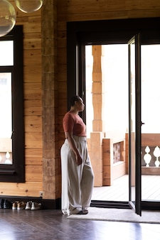 Joven mujer afroamericana mirando por la ventana