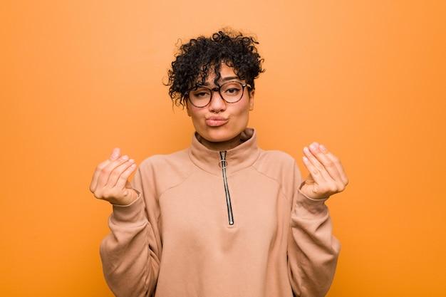 Joven mujer afroamericana mixta contra un fondo marrón que muestra que no tiene dinero.