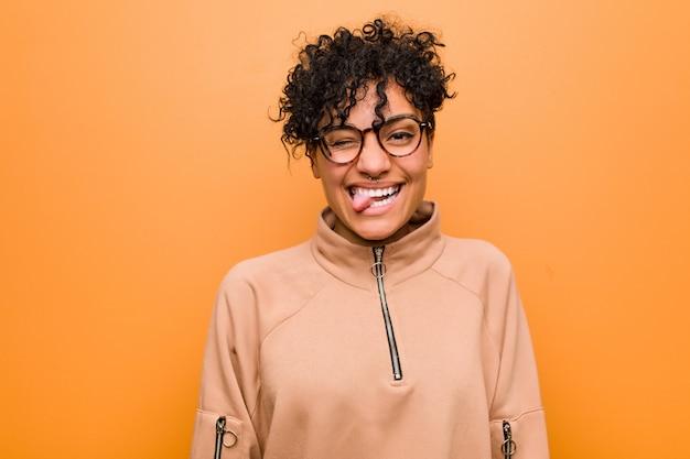 Joven mujer afroamericana mixta contra una pared marrón divertida y amigable sacando la lengua.