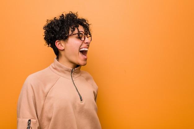 Joven mujer afroamericana mixta contra una pared marrón gritando hacia un espacio de copia
