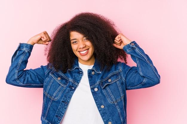 Joven mujer afroamericana mostrando fuerza gesto con brazos, símbolo del poder femenino