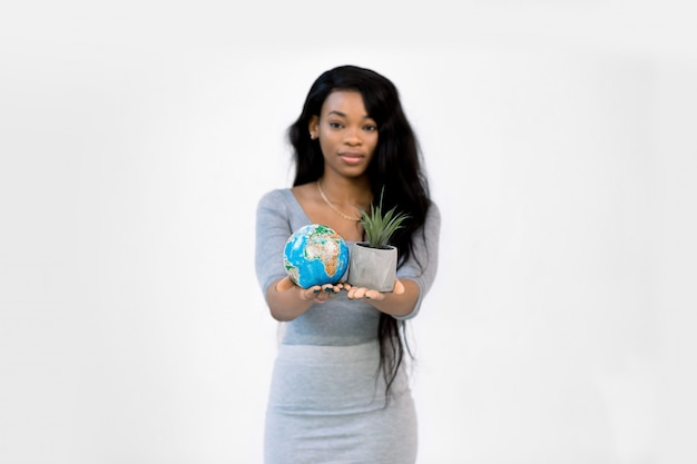 Joven mujer afroamericana mostrando un pequeño globo terráqueo en una mano y una pequeña maceta gris con planta en otra