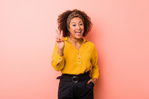 Joven mujer afroamericana mostrando el signo de la victoria y sonriendo ampliamente