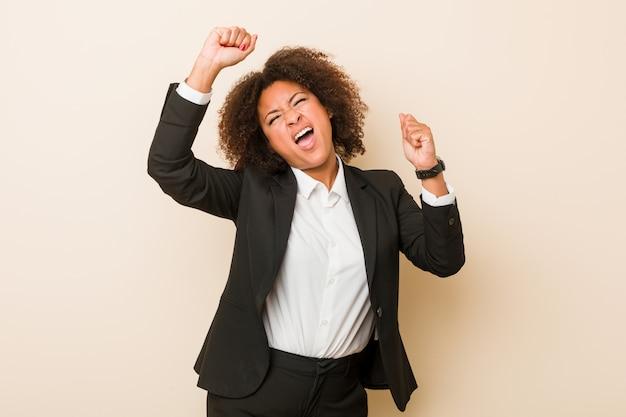 Joven mujer afroamericana de negocios celebrando un día especial, salta y levanta los brazos con energía.