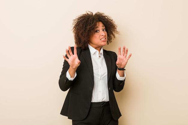 Joven mujer afroamericana de negocios rechazando a alguien que muestra un gesto de asco.