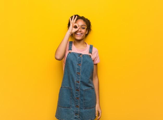Joven mujer afroamericana negra con ojos azules seguros haciendo gesto bien en ojo