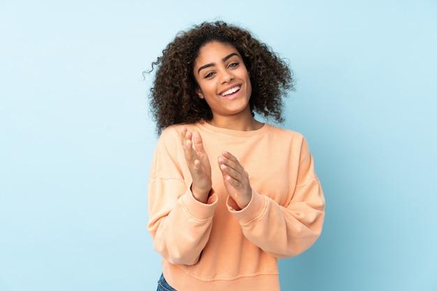 Joven mujer afroamericana en pared azul aplaudiendo después de la presentación en una conferencia