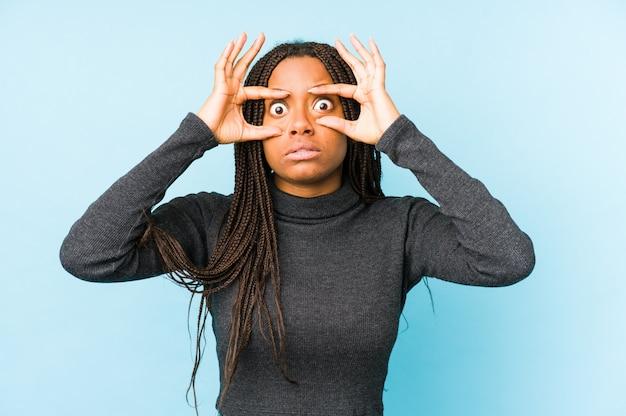 Joven mujer afroamericana en la pared azul manteniendo los ojos abiertos para encontrar una oportunidad de éxito.