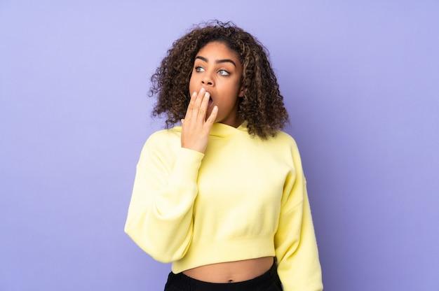 Joven mujer afroamericana en la pared bostezando y cubriendo la boca abierta con la mano