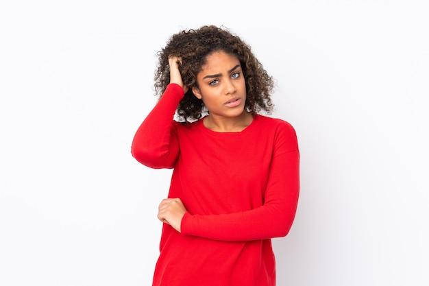Joven mujer afroamericana en pared con dudas