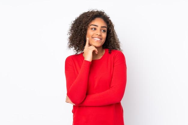 Joven mujer afroamericana en la pared pensando una idea mientras mira hacia arriba
