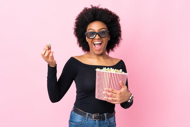 Joven mujer afroamericana en pared rosa con gafas 3d y sosteniendo un gran cubo de palomitas de maíz