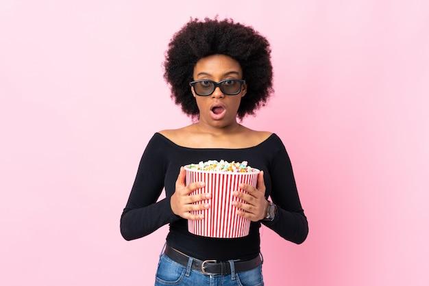 Joven mujer afroamericana en pared rosa sorprendido con gafas 3d y sosteniendo un gran cubo de palomitas de maíz