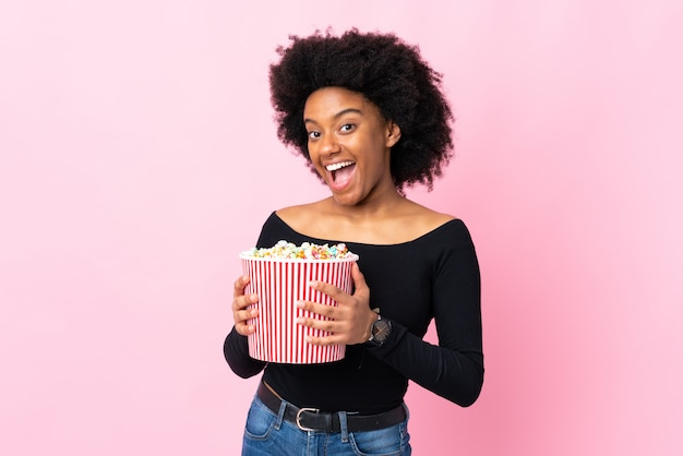 Joven mujer afroamericana en pared rosa sosteniendo un gran cubo de palomitas de maíz