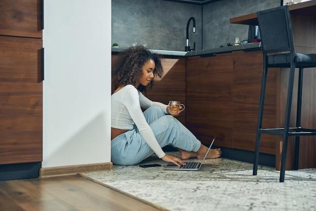 Joven mujer afroamericana pasar tiempo en la cocina mientras trabaja en la computadora portátil y bebe té